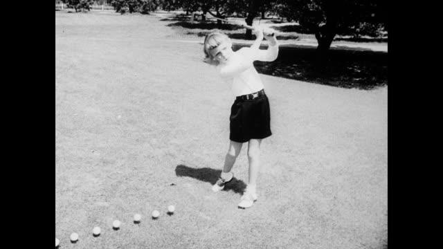 stockvideo's en b-roll-footage met / six year old blonde girl linda lewis hitting golf balls in a row / girl's father chris lewis hitting golf balls in the background / father teaches... - linda lewis