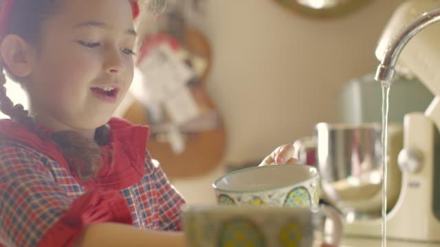 a six year old girl kneeling on a chair whilst washing dishes in a kitchen sink - endast flickor bildbanksvideor och videomaterial från bakom kulisserna