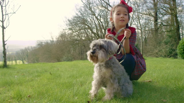A six year old girl with a dog on a leash in a garden