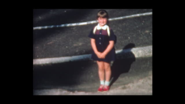 1967 six year old girl with backpack waits for bus - first day of school stock videos & royalty-free footage