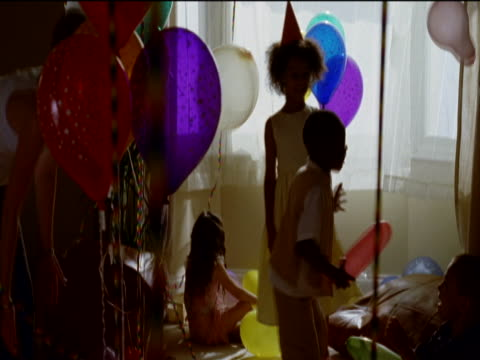 vídeos de stock, filmes e b-roll de six young children and a woman play with multi-coloured balloons in a living room at a birthday party - janela saliente