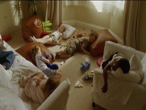 vídeos de stock, filmes e b-roll de six young children asleep in an untidy living room - almofada