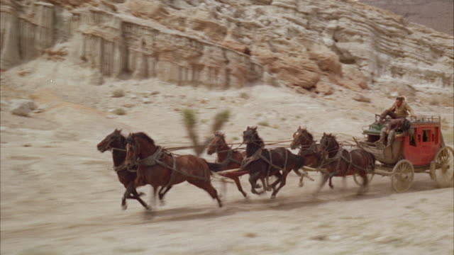 vidéos et rushes de ms six-horse stagecoach moving fast pursuing by small group of riders - ouest américain