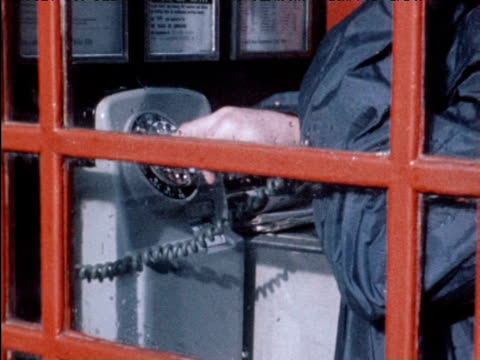 sixpence pushed into parking meter phone box and launderette dryer; 1970 - telefonzelle stock-videos und b-roll-filmmaterial