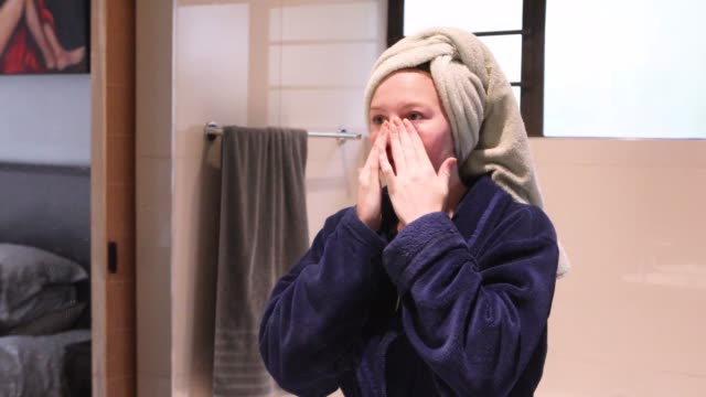 a sixteen-year-old girl washing her face after showering. - wrapped in a towel stock videos & royalty-free footage
