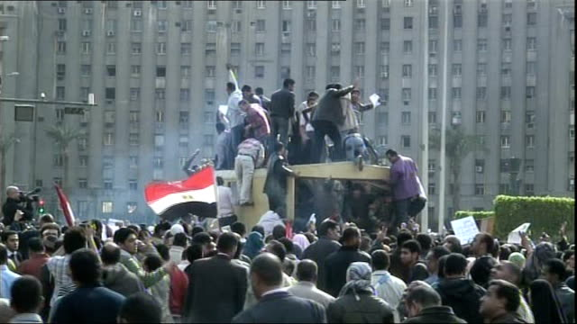 vídeos de stock, filmes e b-roll de military moves more tanks into cairo ext military helicopter overhead egyptian people by burnt out car wreckage freedom square crowds of... - arab spring