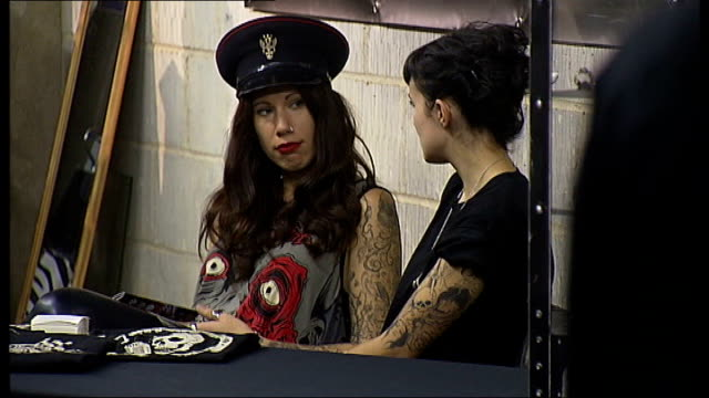 vídeos y material grabado en eventos de stock de sixth international tattoo convention, london; england: london: wapping: tobacco dock: ext man and woman chatting at convention woman with tattoo on... - feria comercial