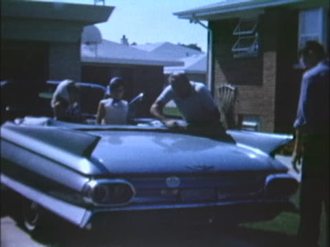vídeos de stock, filmes e b-roll de sixties home movie of two young teen girls in a cadillac being cleaned. - cadillac