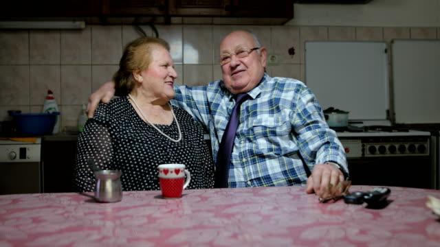 sechzig jahre zusammen. gerne älteres paar im wohnzimmer. lächeln, umarmen und küssen - vergangenheit stock-videos und b-roll-filmmaterial