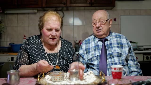 vidéos et rushes de soixante années de vie commune. senior couple partage les fruits confits - exploit sportif
