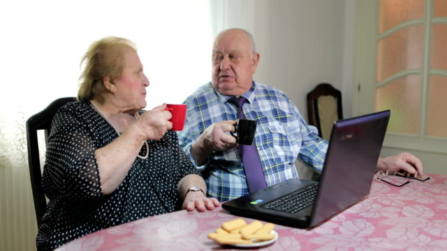 Sixty years together.Senior couple using laptop at home drink coffee and eat biscuits