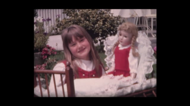 vidéos et rushes de 1967 six-year old girl proudly shows doll and crib - jouet