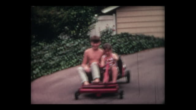 1967 six-year old girl steers go cart down driveway