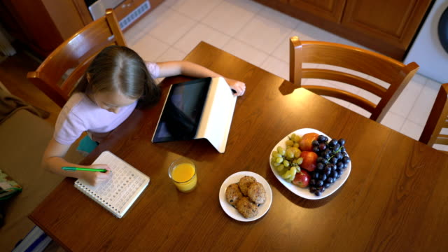 six-year old girl writing in her notebook and browsing on the tablet - homework stock videos & royalty-free footage