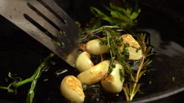 sizzling garlic, rosemary and tarragon roasting in olive oil - garlic stock videos & royalty-free footage
