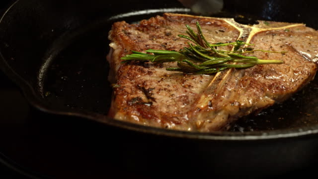 sizzling t-bone steak on a cast iron skillet with herbs and garlic - steak stock videos & royalty-free footage