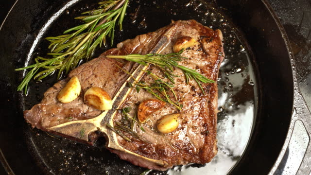 sizzling t-bone steak on a cast iron skillet with herbs and garlic - comfort food stock videos & royalty-free footage