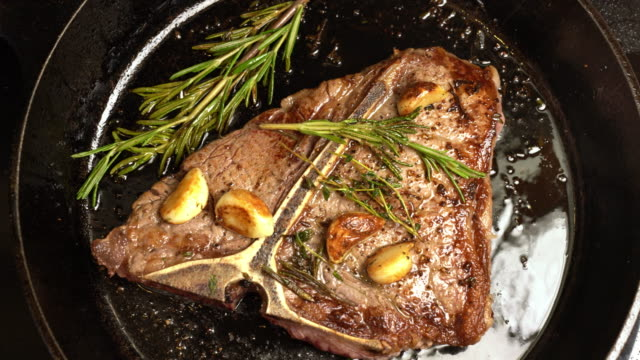 Sizzling T-Bone Steak on a cast iron skillet with herbs and Garlic