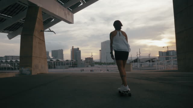 skate girl runs out of the camera in a urban city scape - white shirt stock videos & royalty-free footage