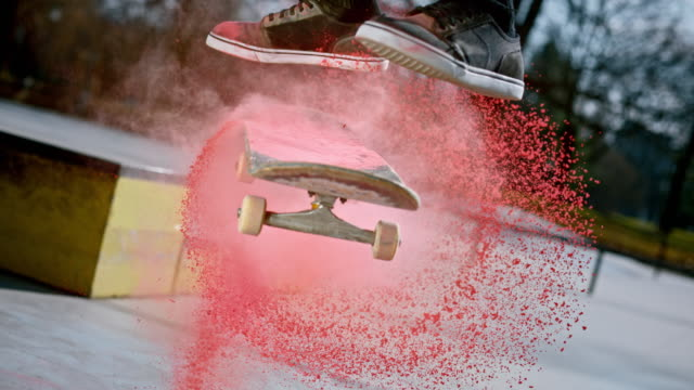 slo mo skateboard being flipped around and red dust is scattered into the air in sunshine - exhilaration stock videos & royalty-free footage