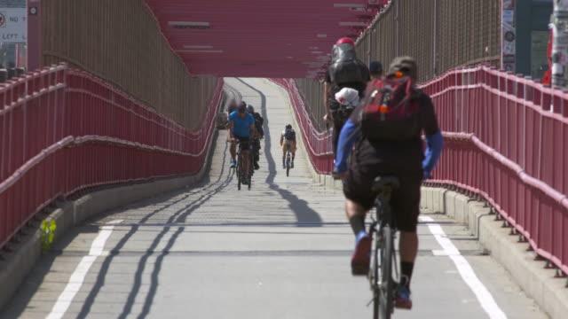 Skateboarder and cyclists use the bike path along the Williamsburg Bridge in Brooklyn.