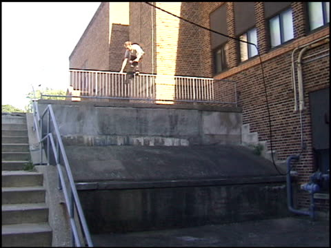 / skateboarder balancing skateboard on a railing and jumping to the ground but falling hard onto the concrete Skateboarder falling onto concrete on...