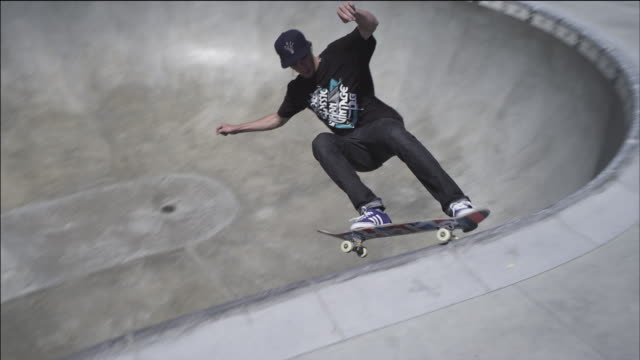 Skateboarder carvers around the bowl, up and down banks; performs various grinds and slides on the coping.
