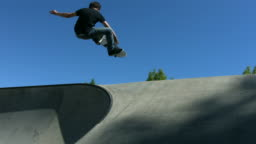 Skateboarder catches air, slow motion