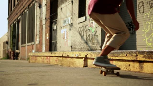 Skateboarder doing trick on sidewalk