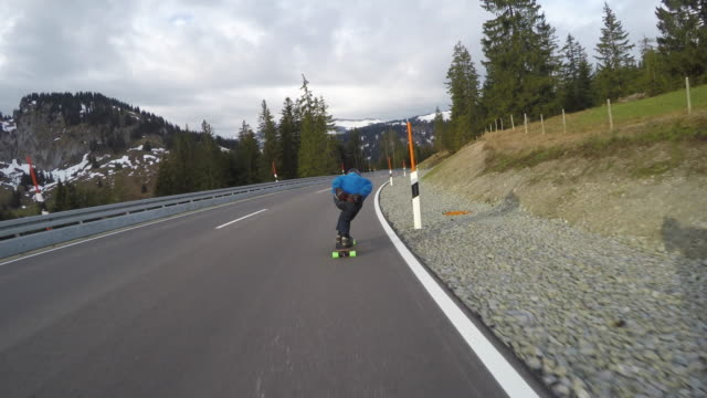 A skateboarder downhill skateboarding on a mountain highway road.