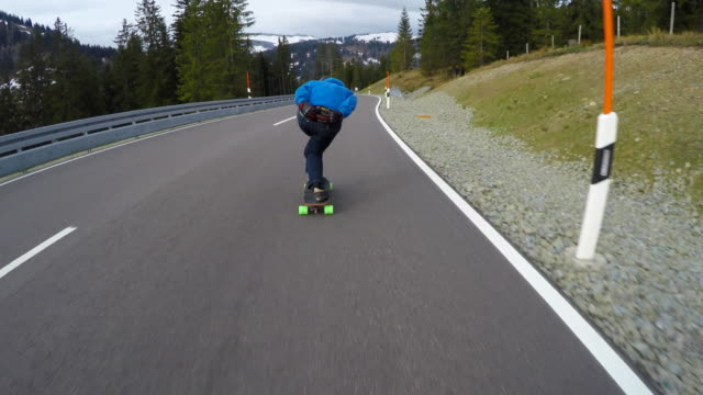 a skateboarder downhill skateboarding on a mountain highway road. - extreme sports stock videos & royalty-free footage