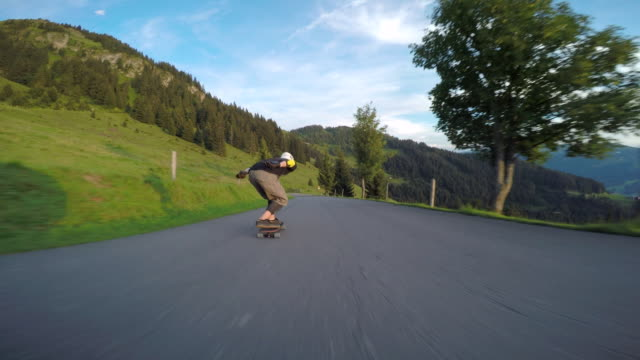 a skateboarder downhill skateboarding on a mountain road. - rasen stock-videos und b-roll-filmmaterial