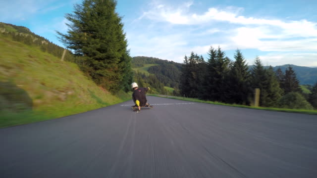 a skateboarder downhill skateboarding on a mountain road. - gefahr stock-videos und b-roll-filmmaterial