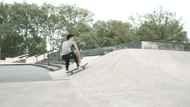 a skateboarder falls at a skatepark in queens - nyc - 4k - slow motion - スケートボード点の映像素材/bロール