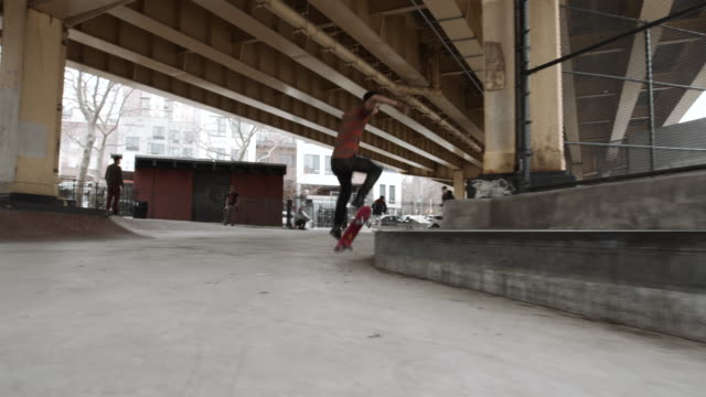 a skateboarder falls performing a trick at a skatepark in brooklyn, nyc - 4k - stunt stock videos & royalty-free footage