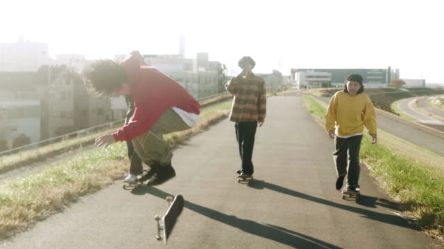 vídeos de stock e filmes b-roll de skateboarder filming friends performing skateboarding tricks (slow motion) - somente japonês