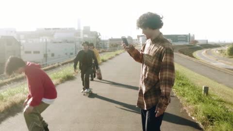 skateboardåkare filmar vänner utför skateboard tricks (slow motion) - filma bildbanksvideor och videomaterial från bakom kulisserna