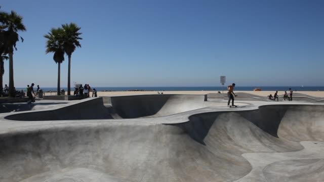 stockvideo's en b-roll-footage met skateboarder in jeans are skateboarding at the skateboard park in venice beach in los angeles. - skateboardpark