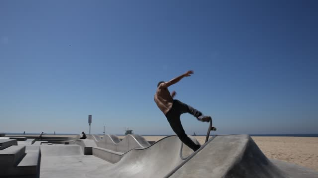 skateboarder in jeans are skateboarding at the skateboard park in venice beach in los angeles. - halfpipe stock-videos und b-roll-filmmaterial