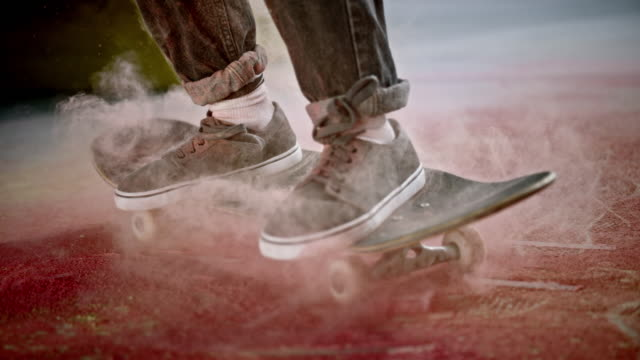 slo mo ld skateboarder landing on his skateboard and scattering the red dust on the ground - jeans stock videos & royalty-free footage