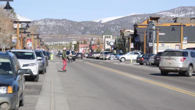 stockvideo's en b-roll-footage met skateboarder rides on frisco street, mountains in background - straatnaambord