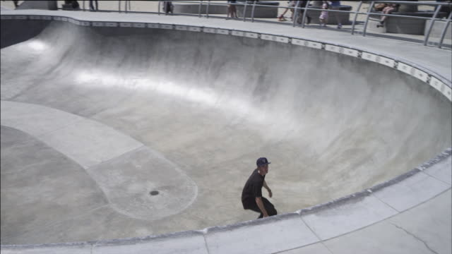 Skateboarder rides toward camera, performs successful grind in close-up.