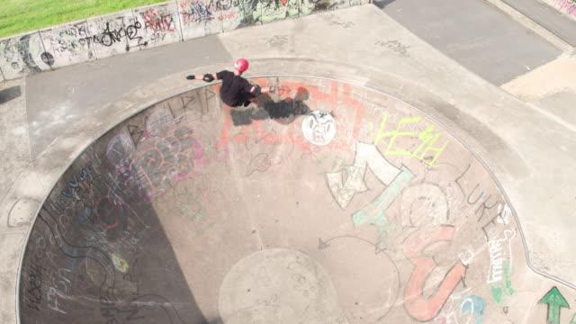 skateboarder riding a bowl at skatepark - 階段点の映像素材/bロール