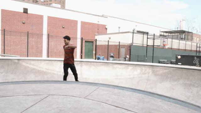a skateboarder shreds a bowl at a skatepark in brooklyn, new york city - 4k - fence点の映像素材/bロール