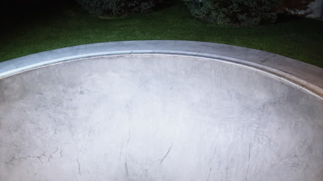 WS Skateboarder sliding ramp in skate park at night / Orem, Utah, USA