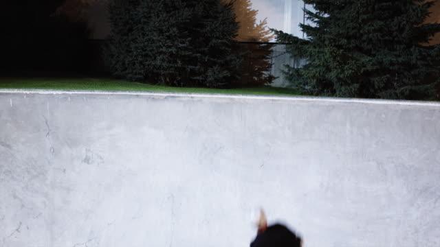 WS SLO MO TU TD Skateboarder sliding ramp in skate park at night / Orem, Utah, USA