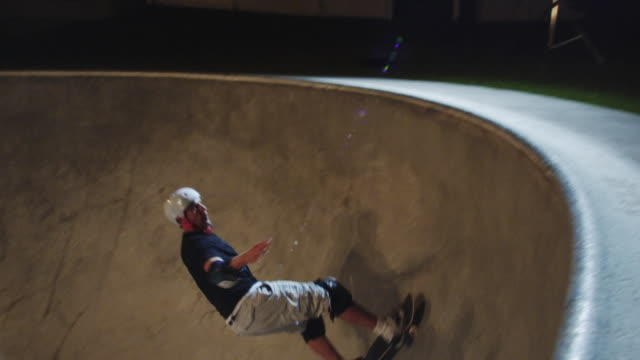 WS PAN SLO MO Skateboarder sliding ramp in skate park at night / Orem, Utah, USA