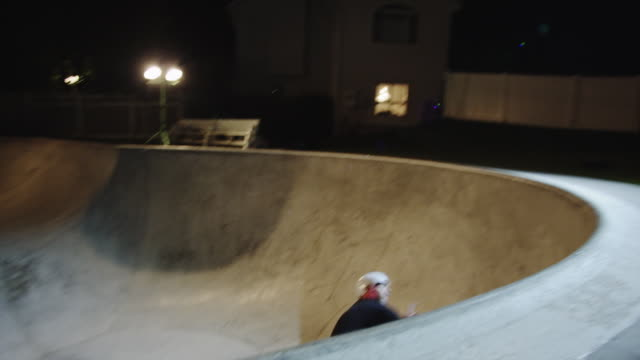 WS PAN Skateboarder sliding ramp in skatepark at night / Orem, Utah, USA