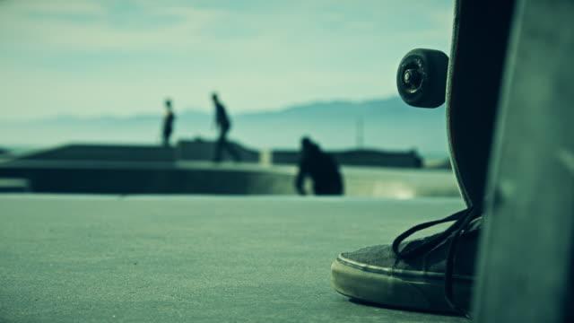 Skateboarder Watching Friends