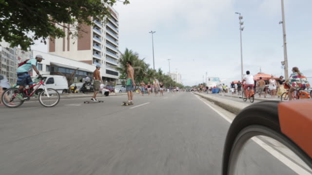 pov, ws skateboarders and cyclists ride along ipanema beach / rio de janeiro, brazil - following stock videos and b-roll footage